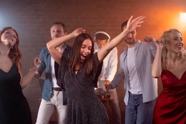 Fermez les amis souriants dansant au bar