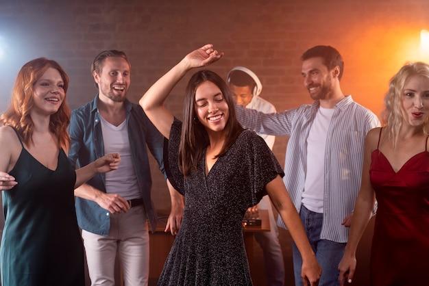 Fermez les amis souriants dansant