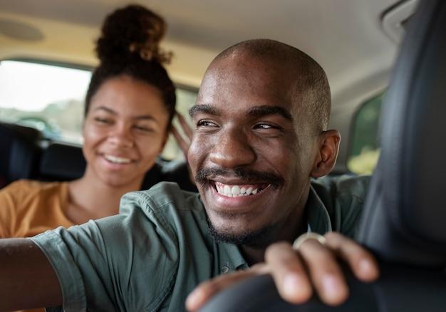 Fermez les amis souriants à l'intérieur de la voiture