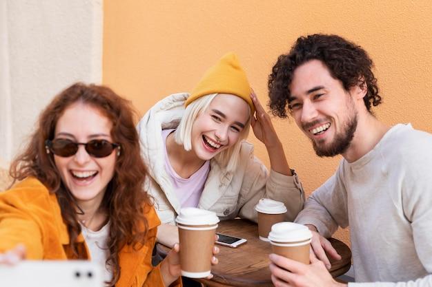Fermez les amis souriants prenant le selfie