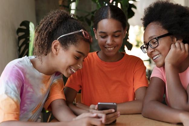 Fermez les amis souriants avec le téléphone