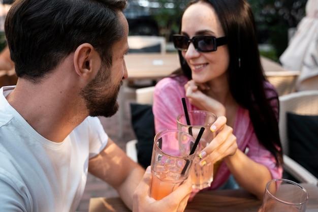 Fermez les amis à table avec des boissons