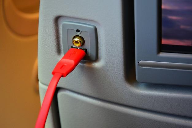 Fermez le chargeur de prise usb et le port auxiliaire avec un câble usb rouge à l'arrière du siège de l'avion