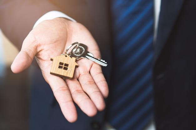 Fermez les clés de la vue principale dans la main de l'agent donnant au nouveau propriétaire.