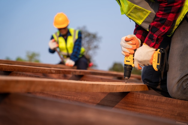 Fermez le couvreur travaillant sur la structure du toit du bâtiment sur le chantier de construction, couvreur utilisant un pistolet à clous pneumatique ou pneumatique et installant sur une structure de toit en bois.