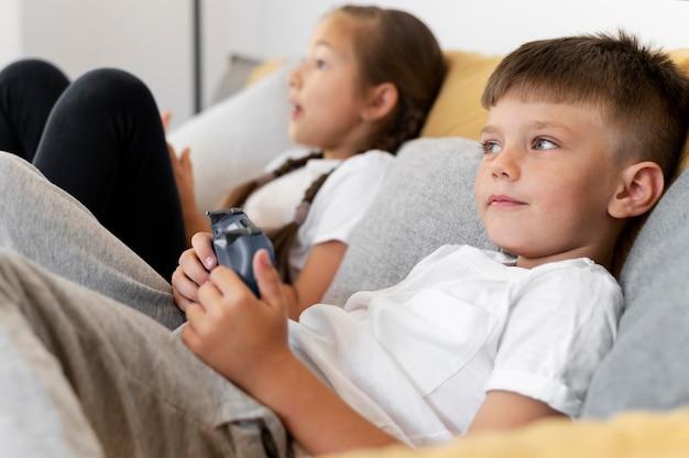 Fermez les enfants jouant avec des contrôleurs