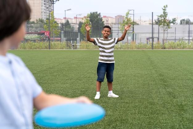 Fermez les enfants jouant avec le frisbee