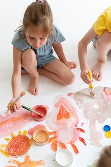 Fermez les enfants peignant ensemble