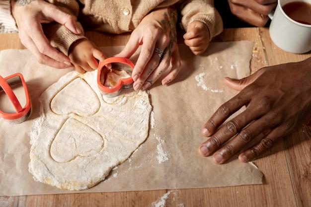 Fermez la famille et l'enfant faisant des biscuits