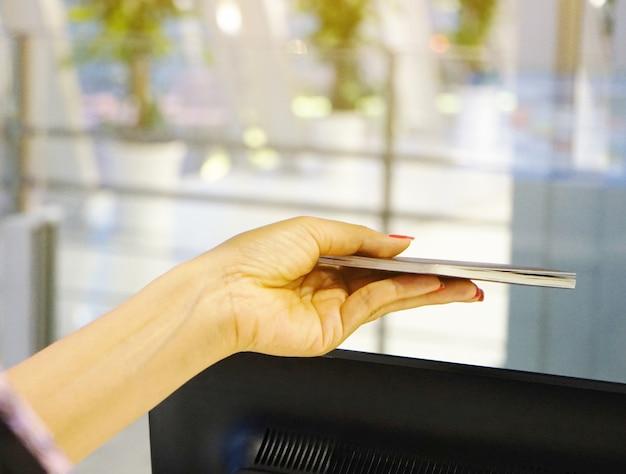 Fermez une femme avec un passeport visible au comptoir d'enregistrement de l'aéroport international.