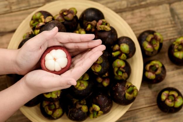 Fermez un fruit de mangoustan prêt à manger sur une belle main.