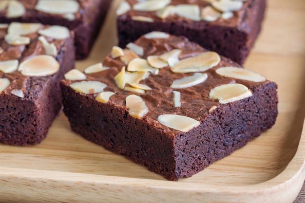 Fermez la garniture de brownies au chocolat noir maison avec des tranches d'amandes et sur une assiette en bois.