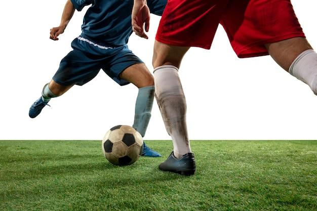Fermez les jambes des joueurs de football professionnels qui se battent pour le ballon