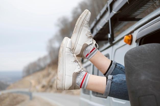 Fermez les jambes par la fenêtre de la voiture