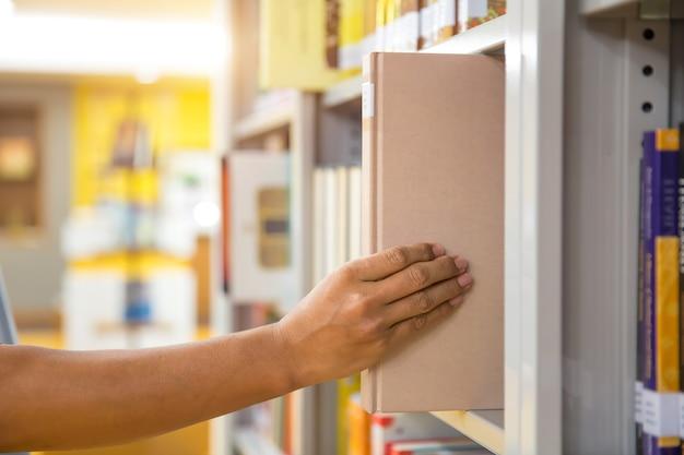 Fermez La Main En Choisissant Un Livre Dans La Bibliothèque. Photo Premium