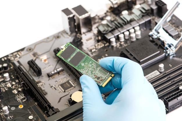 Fermez la main dans un gant bleu en installant le disque dur ssd dans la carte mère.