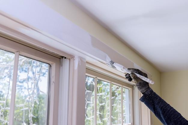 Fermez la main d'un homme dans la peinture d'un cadre de fenêtre de couleur blanche