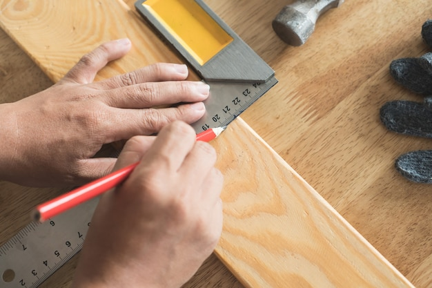 Fermez les mains du charpentier marquant sur bois.
