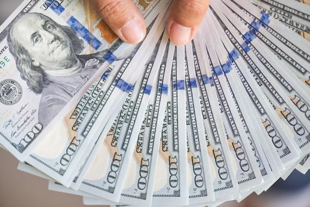 Fermez les mains de femme nous tenant des billets d'un dollar.