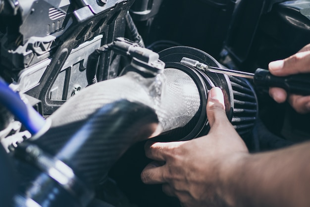 Fermez les mains d'un mécanicien méconnaissable effectuant le service et l'entretien de la voiture. flux d'air changeant