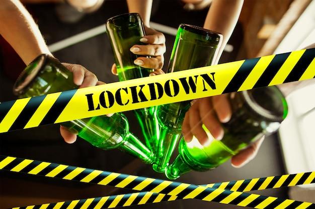 Fermez les mains en tinter des bouteilles avec des bandes de délimitation de bière verrouillage, coronavirus, quarantaine, avertissement - fermeture des bars, restaurants et discothèques pendant la pandémie. vie sociale dégradée, interdiction de réunion de groupe.