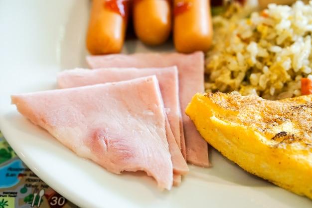 Fermez le petit déjeuner avec des œufs, du pain, du riz frit, de la saucisse et du bacon.