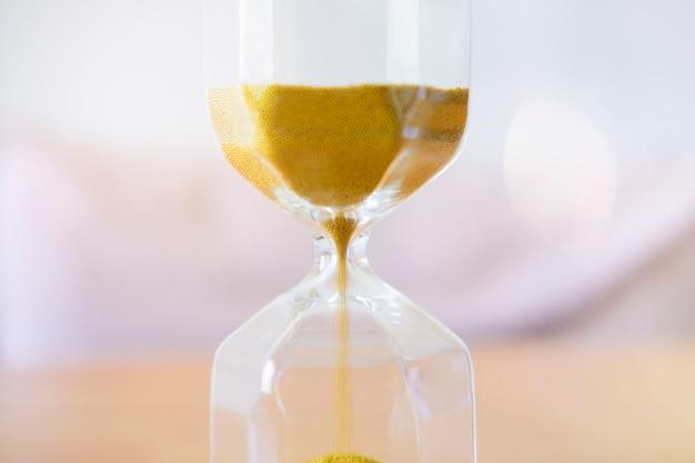 Fermez le sable doré qui traverse les ampoules d'un sablier.