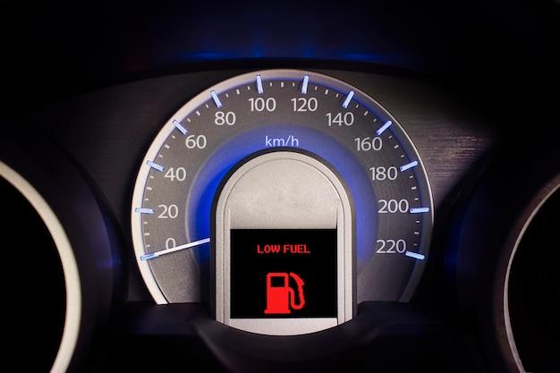 Fermez le tableau de bord d'un compteur de vitesse de voiture et d'un signal de carburant faible.