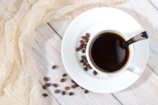 Fermez une tasse de café chaud avec des grains de café torréfiés sur une table en bois blanc.