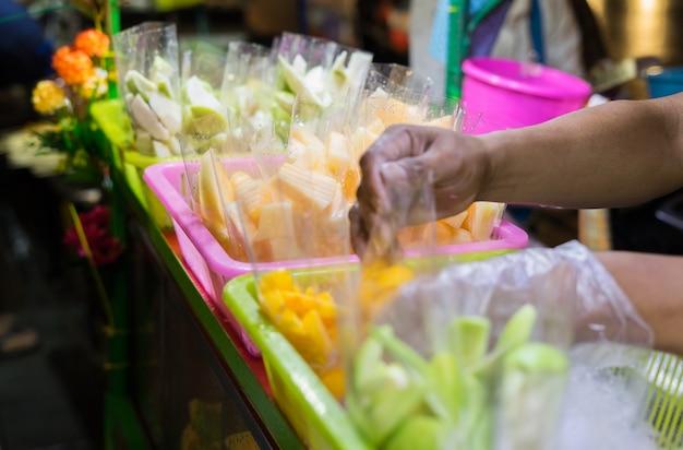 Fermez le vendeur de fruits de la rue le long d'une rue commerçante principale