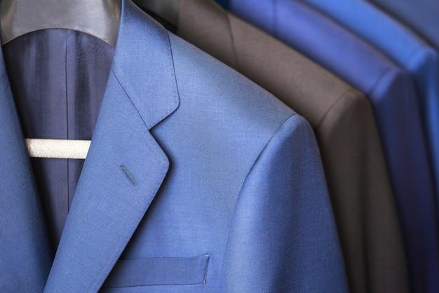 Fermez-vous dans une rangée de costumes de luxe, accrochés dans un placard.