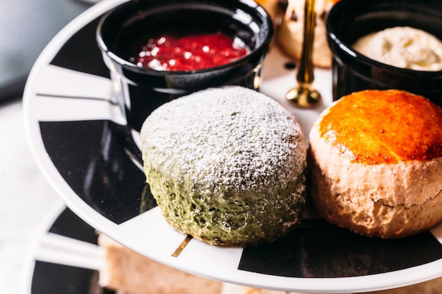 Fermez-vous avec du glaçage au thé vert et du scone ordinaire sur une plaque de couleur noir et blanc.