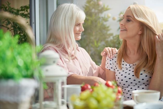 Fermez-vous sur une femme mûre de rêve sur le balcon avec son amie