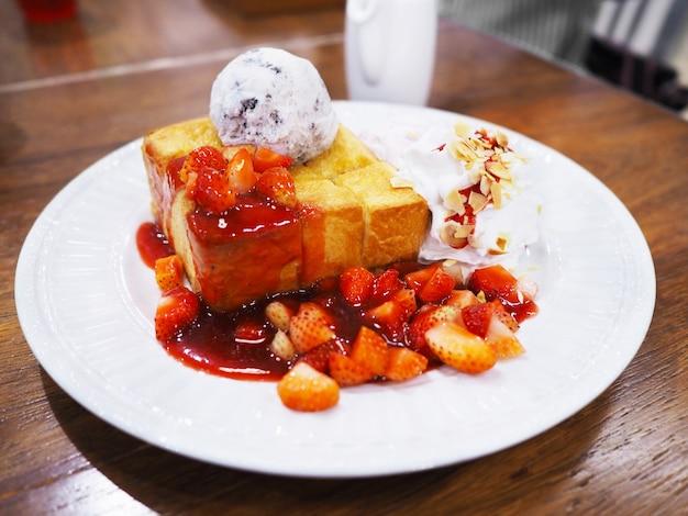 Fermez-vous vers le haut de la crème glacée de pain grillé au miel avec du sirop de fraise en tranches et de la crème fouettée aux amandes sur une plaque blanche.