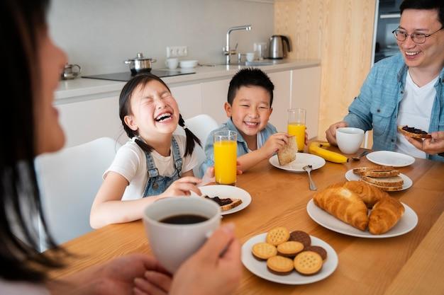Fermez-vous vers le haut de la famille heureuse mangeant ensemble