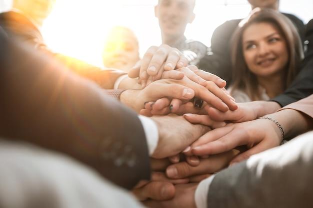 Fermez-vous vers le haut d'un groupe de jeunes gens d'affaires montrant leur unité