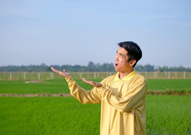 Un fermier asiatique porte une chemise jaune debout et lève la main avec un visage surprise wow à la ferme verte
