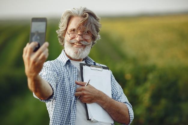 Le fermier examine le champ. l'agronome ou l'agriculteur examine la croissance du blé.