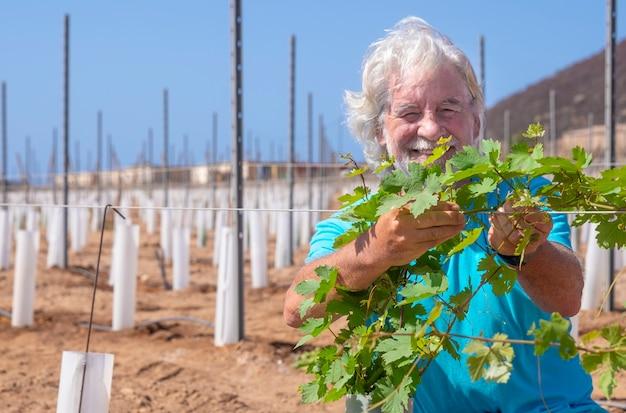 Fermier fier et heureux contrôle la croissance de son nouveau vignoble - homme senior à la retraite actif aux cheveux blancs et à la barbe à la campagne