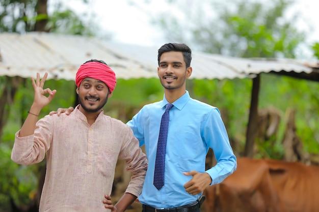 Fermier indien avec agronome dans sa ferme d'élevage
