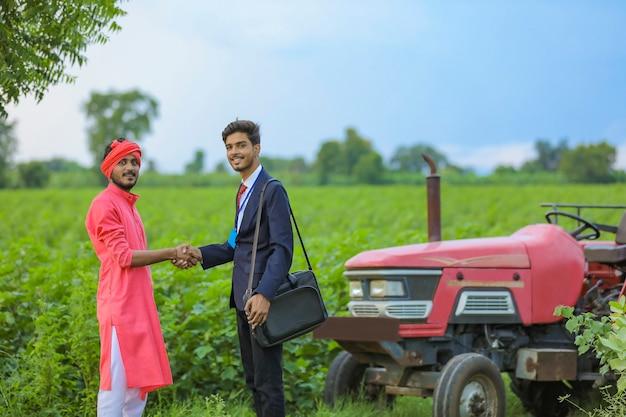 Fermier indien et banquier debout au champ