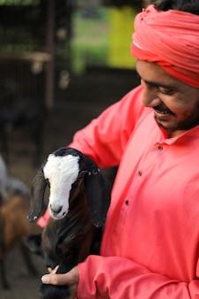 Fermier indien dans une ferme laitière de chèvre