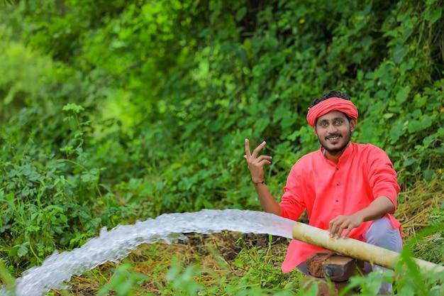 Fermier indien avec écoulement d'eau du tuyau au champ