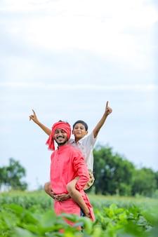 Fermier indien jouant avec son enfant au champ vert