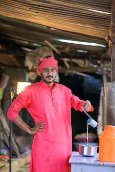 Un fermier indien ou un laitier distribue du lait à la ferme laitière