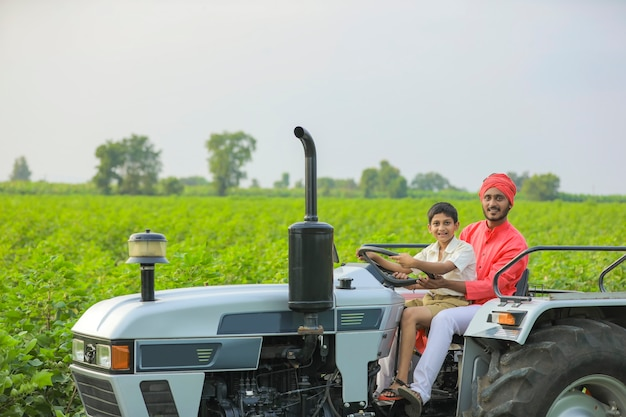 Fermier indien avec son petit enfant travaillant avec tracteur au champ
