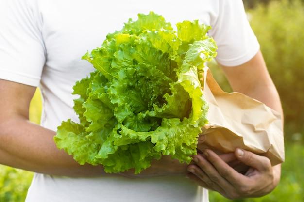Un fermier tient un sac de salade