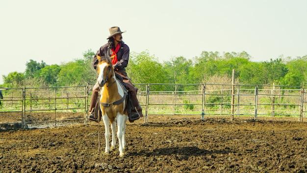 Fermier travaille à la ferme avec des vaches laitières en clôture