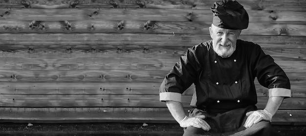 Fermier en uniforme avec des légumes frais sur un fond en bois