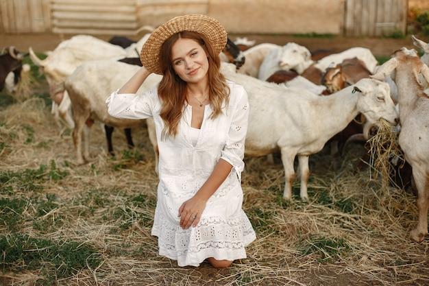 Fermière avec chèvre blanche. femme et petite herbe verte de chèvre. ferme écologique. concept de ferme et d'agriculture. animaux du village. fille joue la chèvre mignonne. f